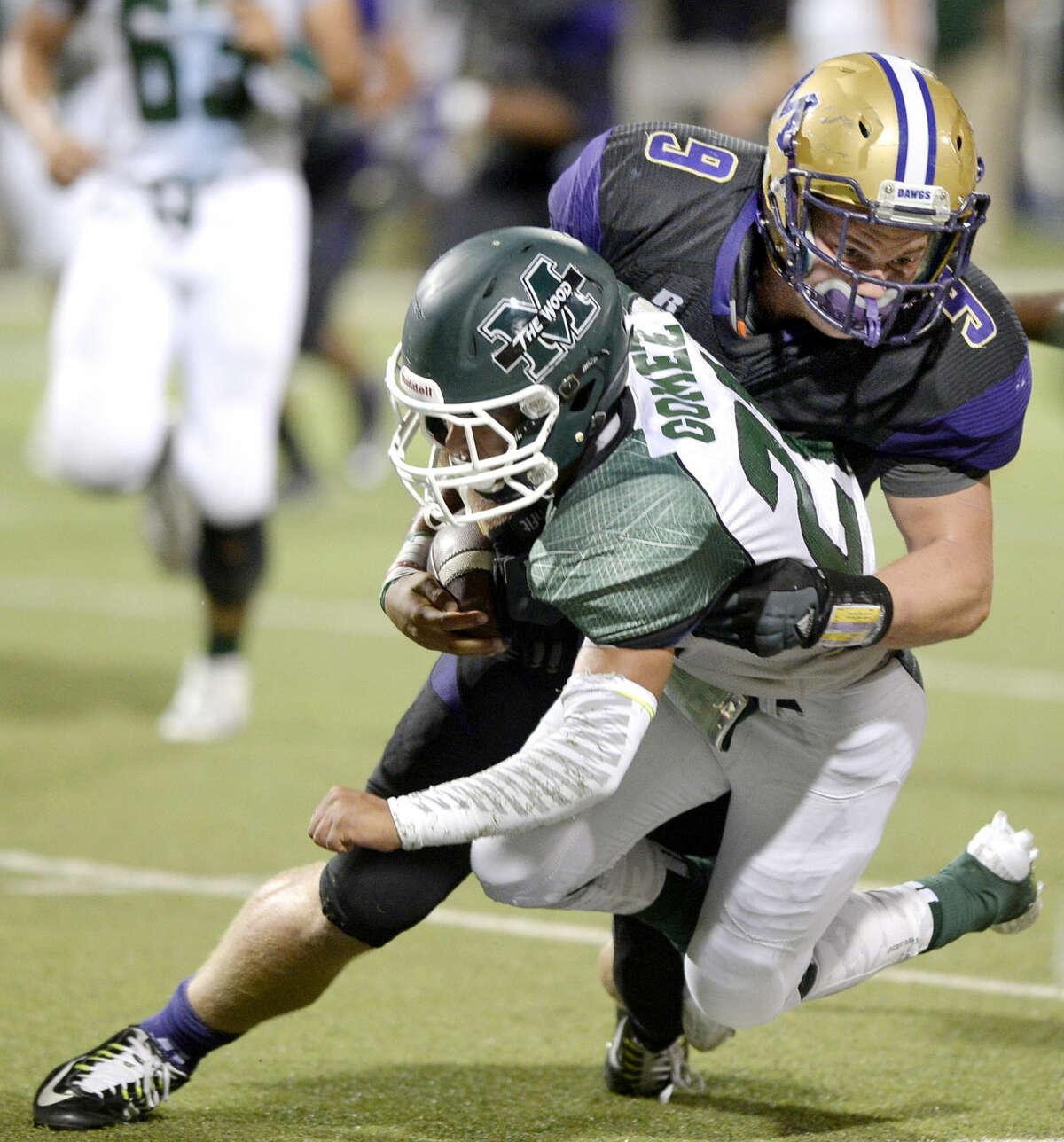 Midland High defensive end Traver Vliem (9) knocks down El Paso Montwood running back Brandon Gomez (21) on Friday, Sept. 4, 2015, at Grande Communications Stadium. James Durbin/Reporter-Telegram