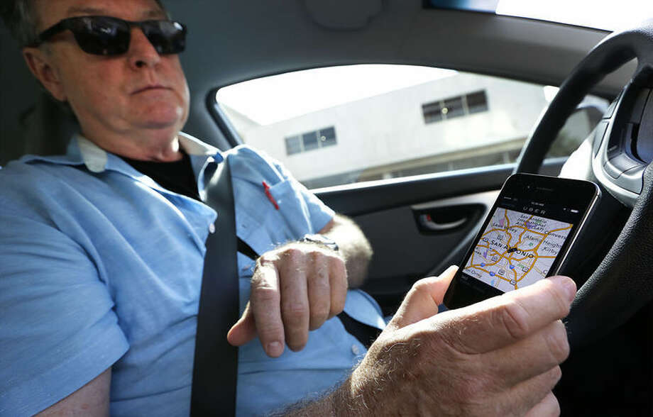Dale Blankenship, an Uber driver, receives Uber calls over a smart phone app. Wednesday, Oct. 8, 2014.