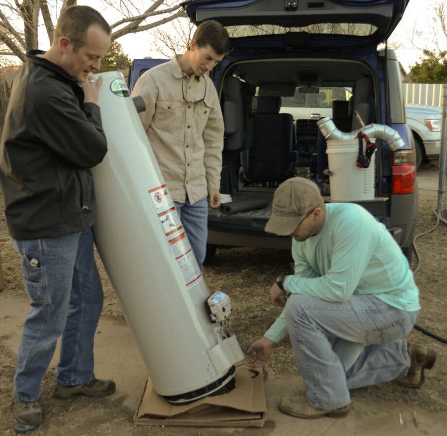 Mark Dean tips back a new water heater as Matt Sears removes the cardboard and Justin Roland helps Tuesday as they work to replace a broken water heater in a home on E. Nobles as part of their Radical Generosity non-profit work. Tim Fischer\Reporter-Telegram Photo: Tim Fischer