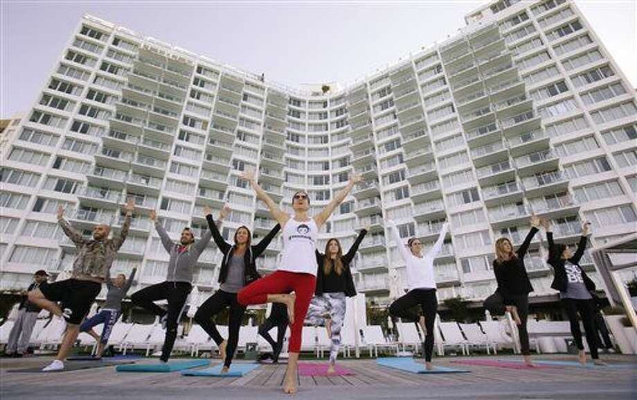 In this Jan. 24, 2016, photo, Paula Walker, center foreground, an instructor with Green Monkey Yoga, leads a yoga class at the Mondrian South Beach Hotel in Miami Beach, Fla. The hotel world is moving beyond basement gyms and ho-hum spa menus to accommodate guests' growing requests to stay healthy while on the road. (AP Photo/Wilfredo Lee) Photo: Wilfredo Lee