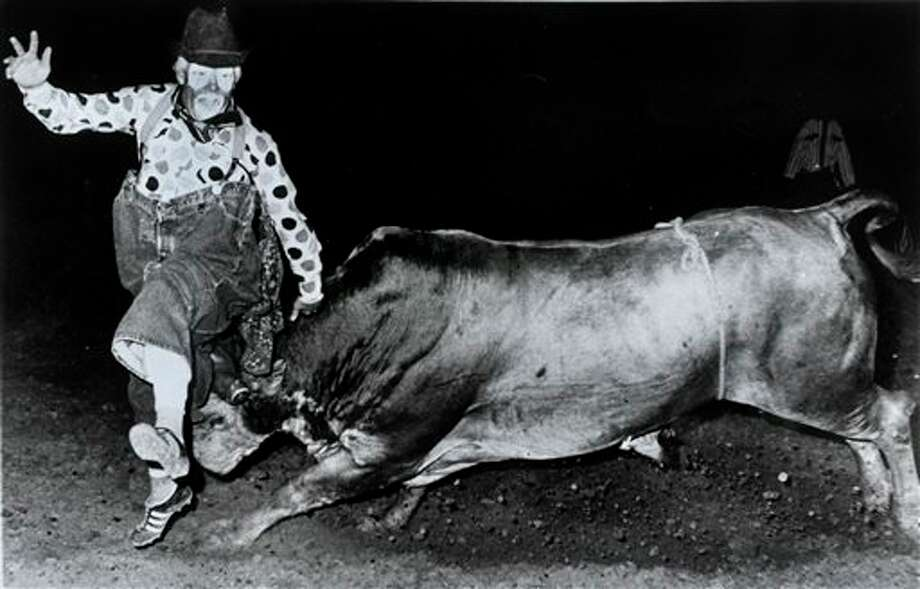 FILE- In this 1970 file photo provided by Quail Dobbs, Quail Dobbs is lifted by a bull during a rodeo in Hill City, Kansas. Dobbs, who spent 35 years as a rodeo clown before becoming a judge in West Texas, has died. He was 72. (AP Photo/Marvin Quail Dobbs, File) Photo: HONS / Marvin Quail Dobbs