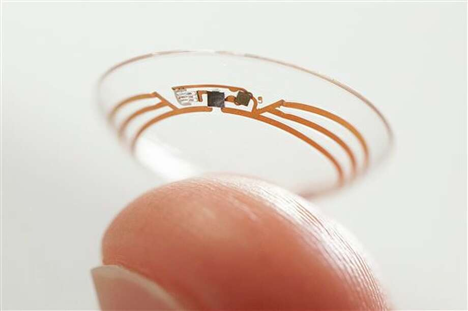 This undated photo released by Google shows a contact lens Google is testing to explore tear glucose. After years of scalding soldering hair-thin wires to miniaturize electronics, Brian Otis, Google X project lead, has burned his fingertips so often that he can no longer feel the tiny chips he made from scratch in Google's Silicon Valley headquarters, a small price to pay for what he says is the smallest wireless glucose sensor that has ever been made. (AP Photo/Google) Photo: Uncredited / AP2013