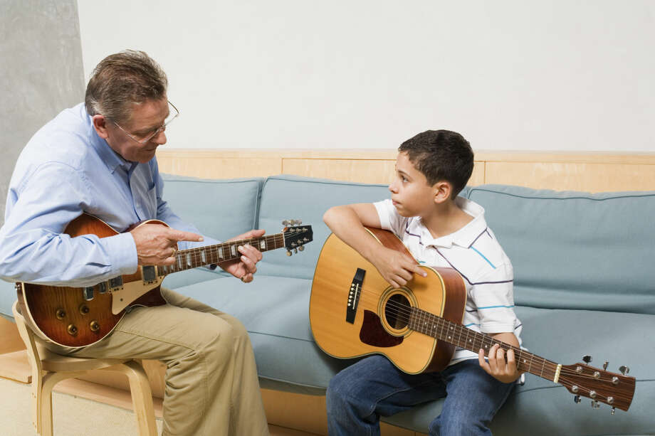 Teacher instructing boy on how to play guitar. Photo: Jupiterimages