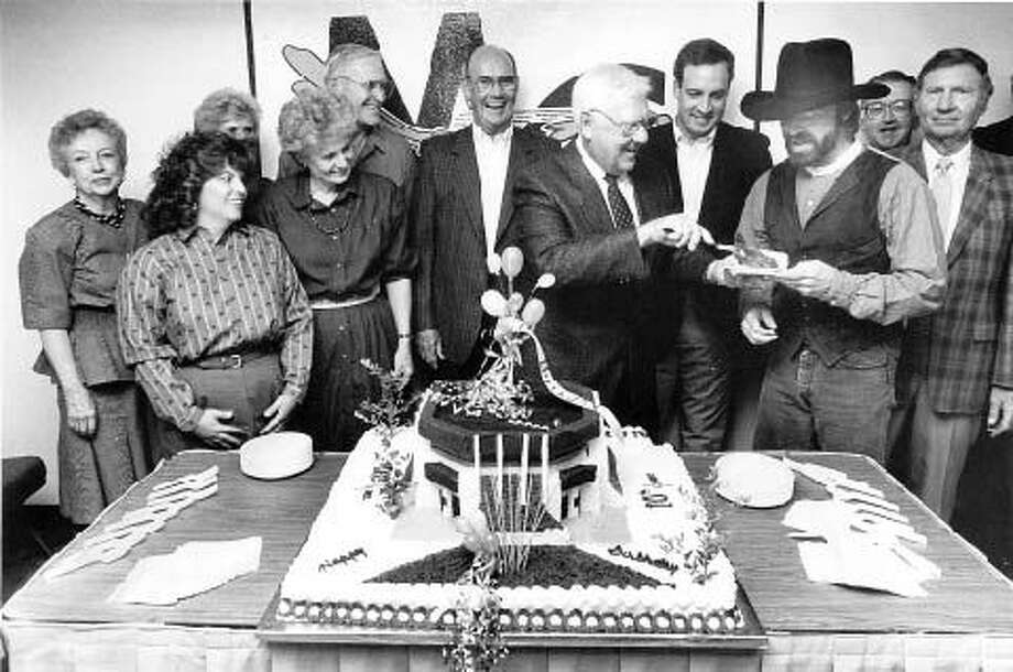 Jess Parrish hands a piece of cake to singer Michael Martin Murphy at the 10-year celebration for the Chaparral Center on Sept. 28, 1988. Photo: File Photo