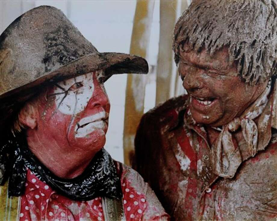 """In this photo provided by Marvin """"Quail"""" Dobbs, Dobbs, left, and fellow rodeo clown Wick Peth laugh after a heavy rain turned the arena in Cheyenne, Wy., into a muddy mess. """"For some reason or another, people like to see other people get out into a mud hole and wrassle,"""" Dobbs said. """"And for two grown men to do it, that's just extra."""" Dobbs, a hall of fame rodeo clown and former Justice of the Peace in Coahoma, passed away Wednesday. (AP Photo/Marvin Quail Dobbs) Photo: HONS / Marvin Quail Dobbs"""