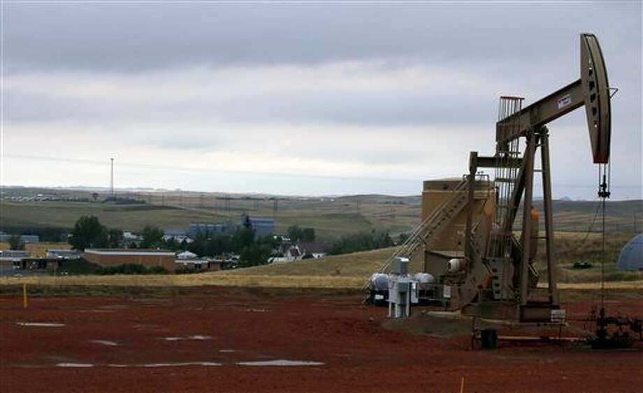 In this Sept. 5, 2015, photo, a pump jack pumps oil on a hill above Alexander, N.D, and the town's school. The U.S., seemingly awash in crude oil after an energy boom sent thousands of workers scurrying to the plains of Texas and North Dakota, will begin exporting oil for the first time since the 1973 oil embargo. (AP Photo/Martha Irvine) Photo: Martha Irvine