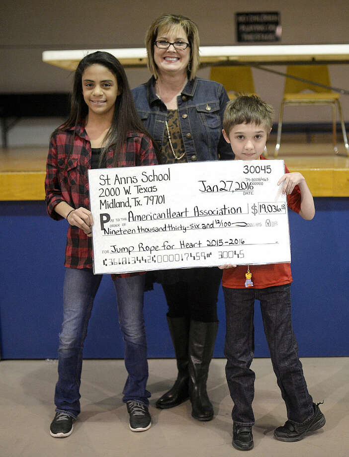 St. Anne's students Aliyah Dickens (left) and Matthew Stout-Martin (right) present a check to Molly Wright (center) of the American Heart Association on Wednesday, Jan. 27, 2016, at St. Anne's. Students jumped rope for the fundraiser and also were allowed to duct tape 5th grade teacher Christine Melendez to a chair as part of the festivities. James Durbin/Reporter-Telegram Photo: James Durbin