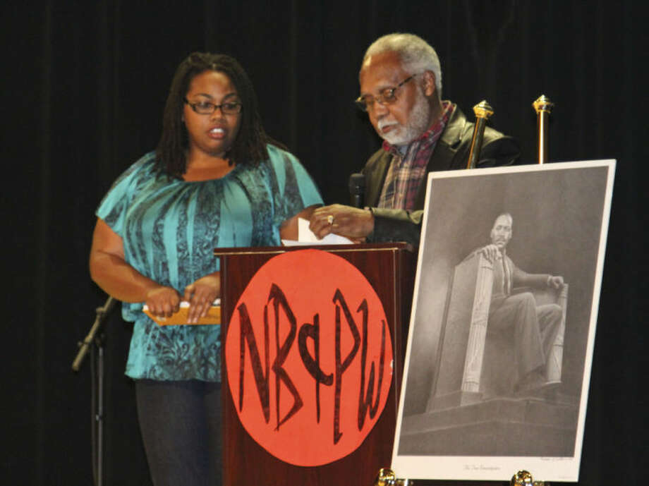 Latisha Williams, left, receives the Martin Luther King Jr. Community Service Award Monday night during a program honoring King's work. Tyler White/Reporter-Telegram Photo: Tyler White
