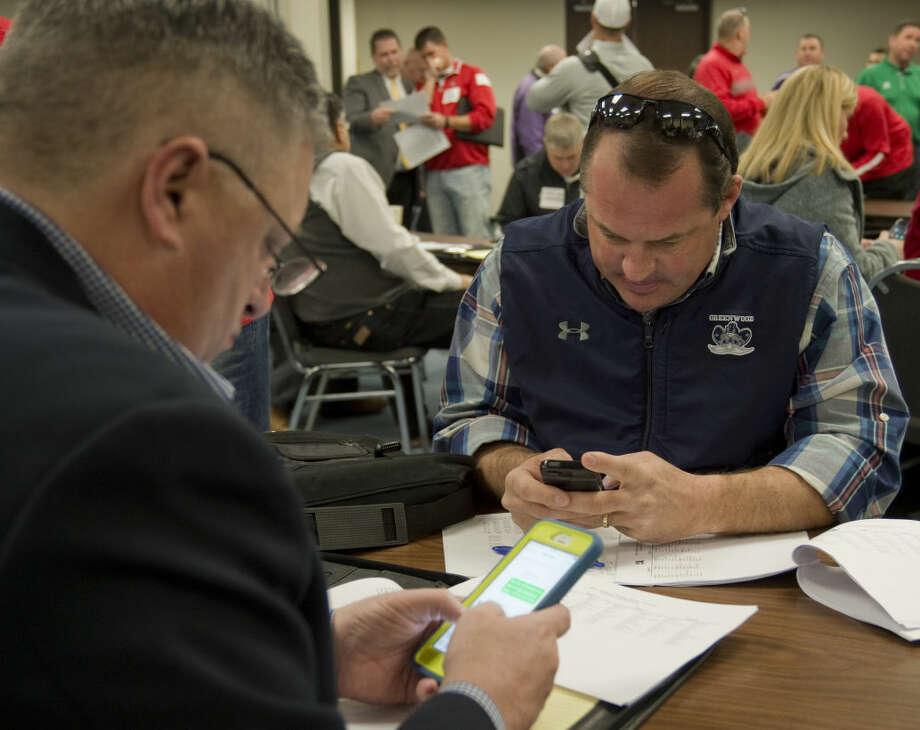 Greenwood coach Shad Hanna and superintendent Edward Elliott make calls after the new UIL districts are released Monday 02-01-16 morning at Region 18 Service Center. Tim Fischer/Reporter-Telegram Photo: Tim Fischer