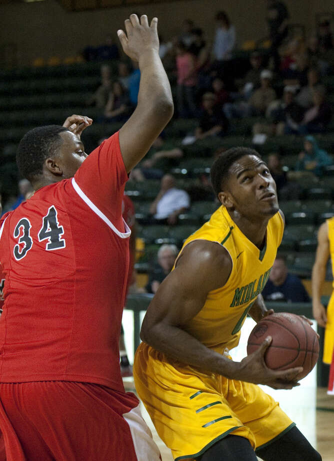 Midland College's Torren Jones goes up for a shot as NMMI's Andre Berry defends Monday, 2-9-15, at the Chaparral Center. Tim Fischer\Reporter-Telegram Photo: Tim Fischer