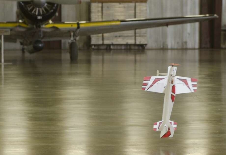 Dennis Robbins practices hovering his foam stunt plane inches off the ground Saturday inside the CAF hanger for the first Fly Day at the museum. Photo by Tim Fischer/Midland Reporter-Telegram Photo: Tim Fischer
