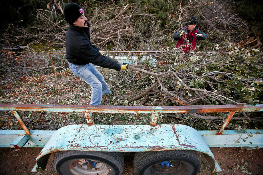 Isaiah Ayala, left, and Sal Olivas, right, unload tree branches from a trailer at the brush drop-off area at Scharbauer Sports Complex, photographed Wednesday, Jan. 7, 2014. James Durbin/Reporter-Telegram Photo: James Durbin