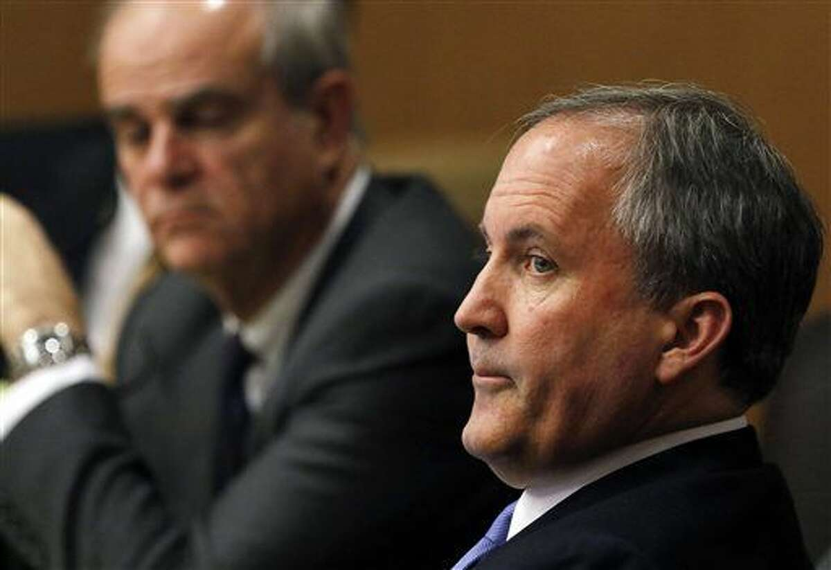 FILE - In this Dec. 1, 2015 file photo, Texas Attorney General Ken Paxton, right, looks at one of the special prosecutors during a pretrial motion hearing at the Collin County courthouse, in McKinney, Texas. Paxton, who says he won't resign despite criminal charges of defrauding investors and a separate investigation into a profitable land deal, may soon let supporters cover his costly legal bills, an arrangement that would skirt the general ban on using donor money for personal use. A state ethics board is expected to decide Monday, Feb. 1 if the Republican can lean on supporters to cover what will likely be a lengthy and expensive courtroom battle. (Jae S. Lee/The Dallas Morning News Via AP, Pool, File)