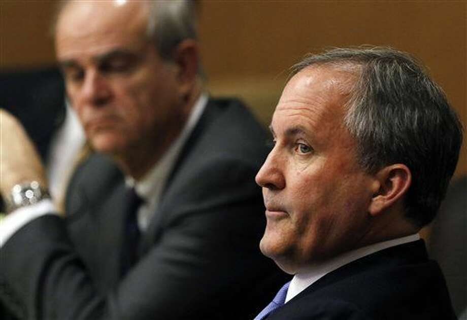 FILE - In this Dec. 1, 2015 file photo, Texas Attorney General Ken Paxton, right, looks at one of the special prosecutors during a pretrial motion hearing at the Collin County courthouse, in McKinney, Texas. Paxton, who says he won't resign despite criminal charges of defrauding investors and a separate investigation into a profitable land deal, may soon let supporters cover his costly legal bills, an arrangement that would skirt the general ban on using donor money for personal use. A state ethics board is expected to decide Monday, Feb. 1 if the Republican can lean on supporters to cover what will likely be a lengthy and expensive courtroom battle. (Jae S. Lee/The Dallas Morning News Via AP, Pool, File) Photo: Jae S. Lee
