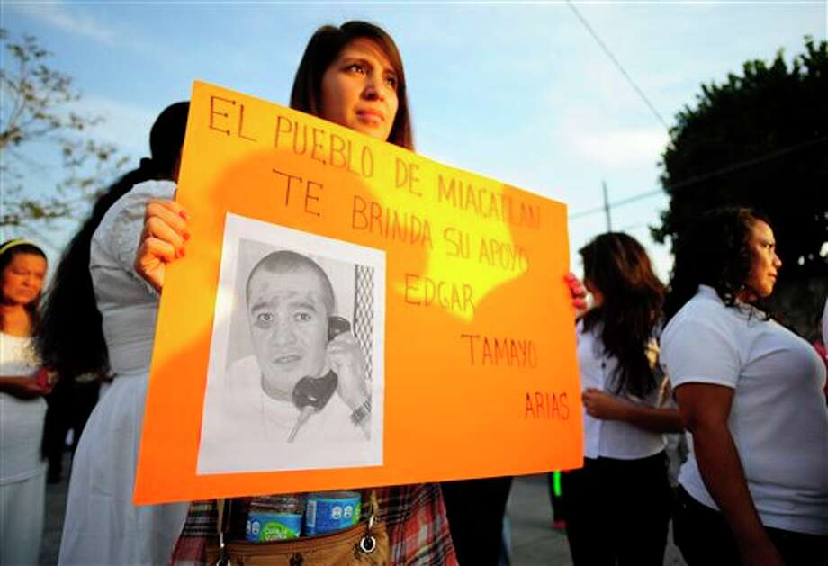 "In this Jan. 19, 2014 photo, a woman holds up a sign showing a photo of Texas death-row inmate Edgar Tamayo that reads in Spanish ""The town of Miacatlan offers you our support, Edgar Tamayo Arias"" during a protest demanding Tamayo's pardon in his hometown of Miacatlan, Mexico. Lawyers for 46-year-old Edgar Tamayo are suing Gov. Rick Perry and the Texas Board of Pardons and Paroles, challenging what they argue is an unfair and secretive clemency process in Texas. Tamayo is set for lethal injection on Wednesday, Jan. 22 in Huntsville. (AP Photo/Tony Rivera) Photo: Tony Rivera / TONY RIVERA2014"