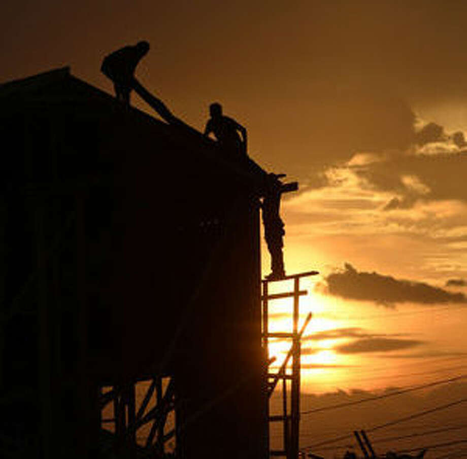 The sun sets behind workers at a home addition project near the intersection of W. New Jersey Ave. and Connell St. on Thursday, Sept. 10, 2015.