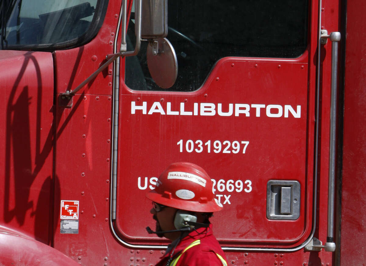 An unidentified worker passes a truck owned by Halliburton at a remote site for natural-gas producer Williams in Rulison, Colo. Halliburton is buying rival oilfield services company Baker Hughes in a cash-and-stock deal worth $34.6 billion, according to reports.
