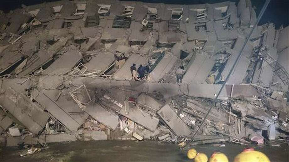 Rescuers are seen entering an office building that collapsed on its side from an early morning earthquake in Tainan, southern Taiwan, Saturday, Feb. 6, 2016. A 6.4-magnitude earthquake has struck southern Taiwan, according to the U.S. Geological Survey. (AP Photo) Photo: STR