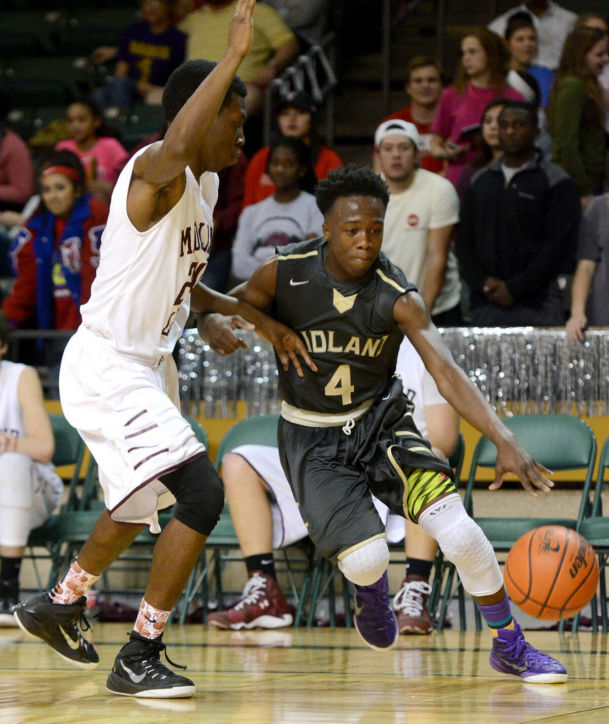 Midland High's A.D. Johnson (4) drives to the hoop against Lee's James Lydia (24) on Tuesday, Feb. 10, 2015 at Chaparral Center. James Durbin/Reporter-Telegram
