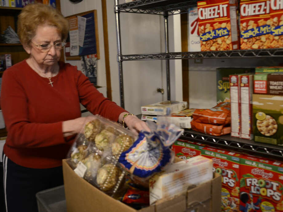 Mae Spencer, one of the volunteers at AMOS, prepares a food basket for a client Wednesday morning. Tim Fischer\Reporter-Telegram Photo: Tim Fischer
