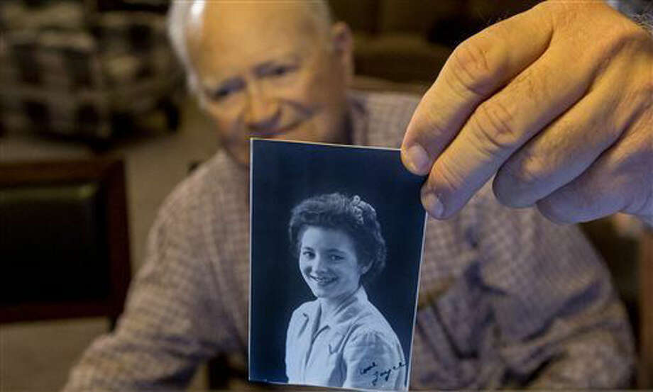 In this photo taken Nov. 6, 2015, Norwood Thomas, 93, holds up a photo of with Joyce Morris at his home in Virginia Beach, Va. During World War II, Morris lived in England and was Joyce Durrant, the girlfriend of Thomas, a D-Day paratrooper with the Army's 101st Airborne Division. Morris now lives in Australia. (Bill Tiernan/The Virginian-Pilot via AP) MAGS OUT; MANDATORY CREDIT Photo: Bill Tiernan