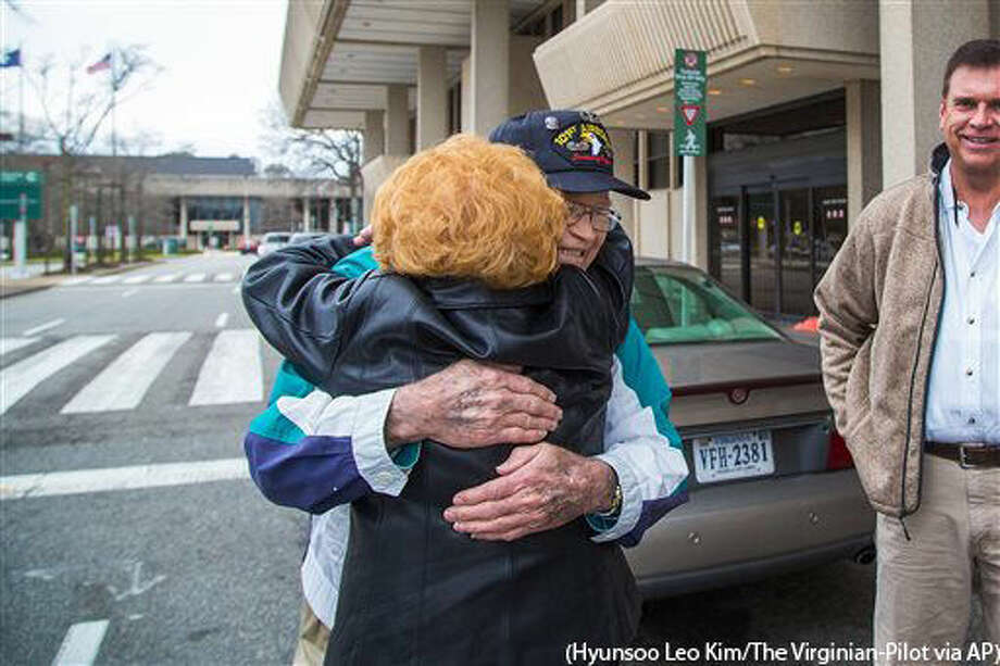In this Sunday, Feb. 7, 2016 photo, Norwood Thomas hugs his neighbor who gave him and his son Steven Thomas, right, ride to Norfolk airport to fly to Australia to reunite with his long lost girlfriend, at the airport in Norfolk, Va. (Hyunsoo Leo Kim/The Virginian-Pilot via AP) MANDATORY CREDIT Photo: Hyunsoo Leo Kim