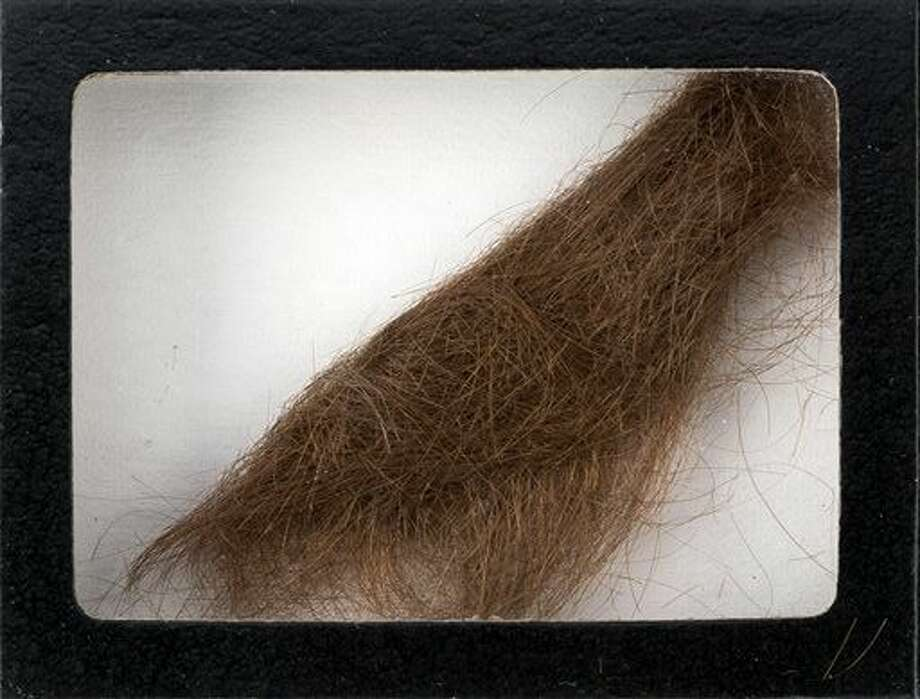 "This photo provided by Heritage Auctions shows a 4-inch lock of hair that was collected by a German hairdresser who trimmed John Lennon's hair before he started shooting ""How I Won the War."" Heritage Auctions says the lock of hair is expected to sell for $10,000 at a Dallas auction later this month. (Heritage Auctions via AP) Photo: HONS"