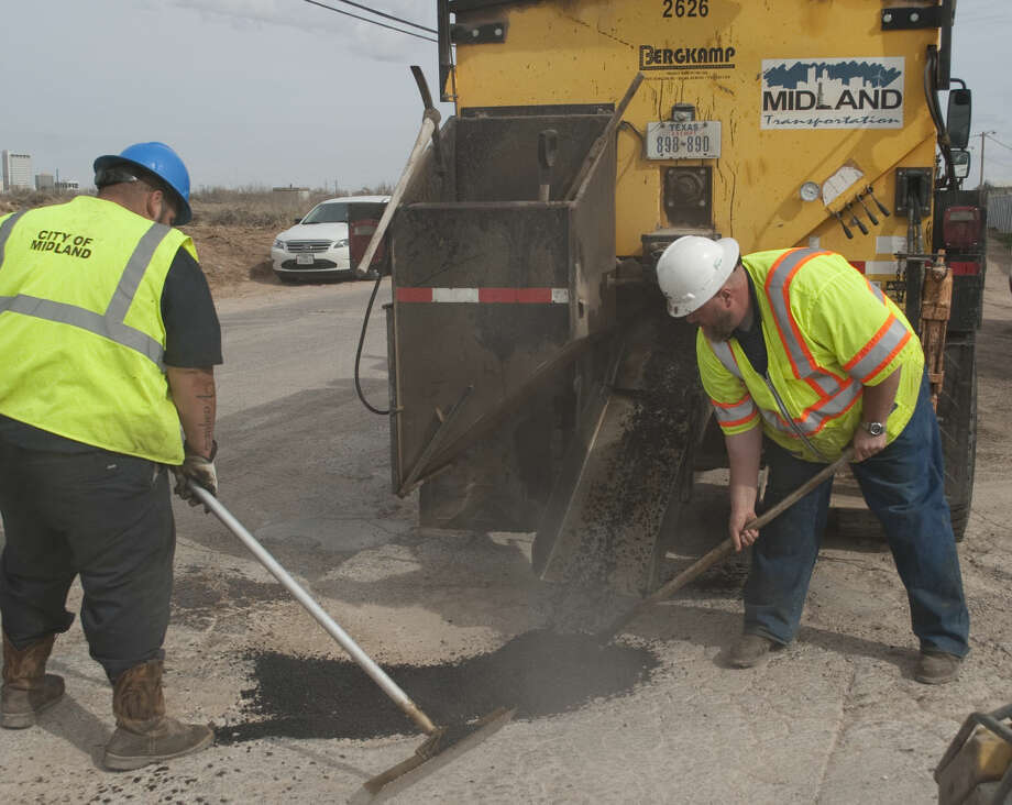 David Vasquez and Abe Langston, white hat, with City of Midland Transportation, fill a pothole with hot asphalt Thursday, 1-29-15, at the intersection of Cotton Flat and Francis. Tim Fischer\Reporter-Telegram Photo: Tim Fischer