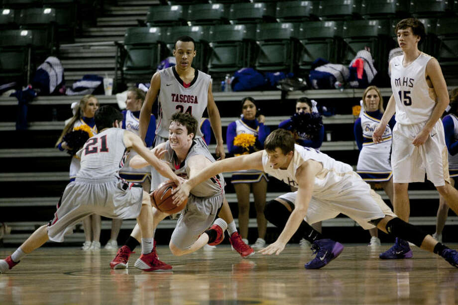 Midland's Trevor Abney (34) chases a loose ball against Amarillo Tascosa's Kris Mincey (21) and Matthew Ratliff (33) on Jan. 24 at Chaparral Center. James Durbin/Reporter-Telegram Photo: JAMES DURBIN