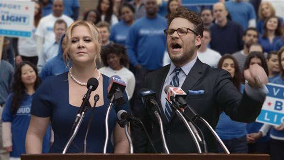 This image provided by Anheuser-Busch shows actors Amy Schumer and Seth Rogen in the company's Bud Light Party campaign spot for Super Bowl 50. (Anheuser-Busch via AP) Photo: HONS