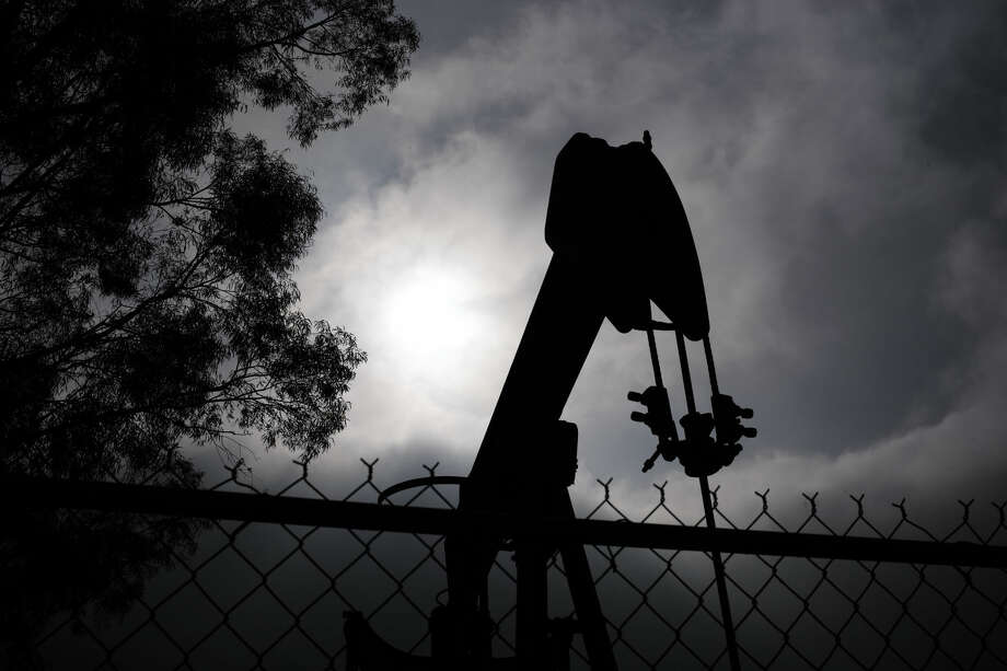 """A pumpjack operates next to Tony Lemon's home, Thursday, Jan. 15, 2015, in Bakersfield, Calif. Lemon and other neighbors living around the idled well said they had been told nothing of any threat to local water. But Lemon said he trusted oil companies to safeguard the public water supply. """"As long as they know what they're doing, taking care of business,"""" Lemon said. (AP Photo/Jae C. Hong) Photo: Jae C. Hong"""