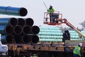 In this May 9, 2015 file photo, workers unload pipes at a staging area in Worthing, S.D., for the proposed Dakota Access Pipeline that would stretch from the Bakken oil fields in North Dakota through South Dakota and Iowa to a hub in Illinois. On Monday, Nov. 30, 2015, the South Dakota Public Utilities Commission is meeting to discuss whether to grant a construction permit for the 1,130-mile pipeline that would move at least 450,000 barrels of crude daily from the Bakken oil patch. (AP Photo/Nati Harnik, File)