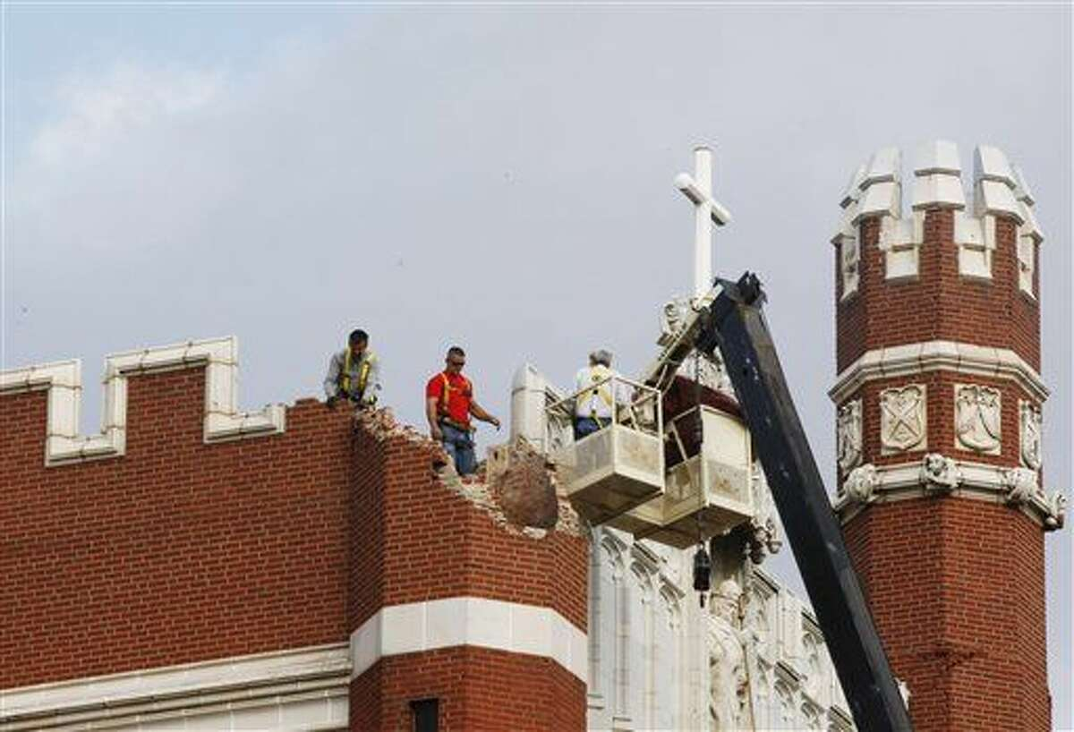 File - In this Nov. 6, 2011 file photo, maintenance workers inspect the damage to one of the spires on Benedictine Hall at St. Gregory's University in Shawnee, Okla., after two earthquakes hit the area in less than 24 hours. New federal research says small earthquakes shaking Oklahoma and southern Kansas daily are dramatically increasing the chance of bigger and dangerous quakes, new federal research indicates. (AP Photo/Sue Ogrocki)
