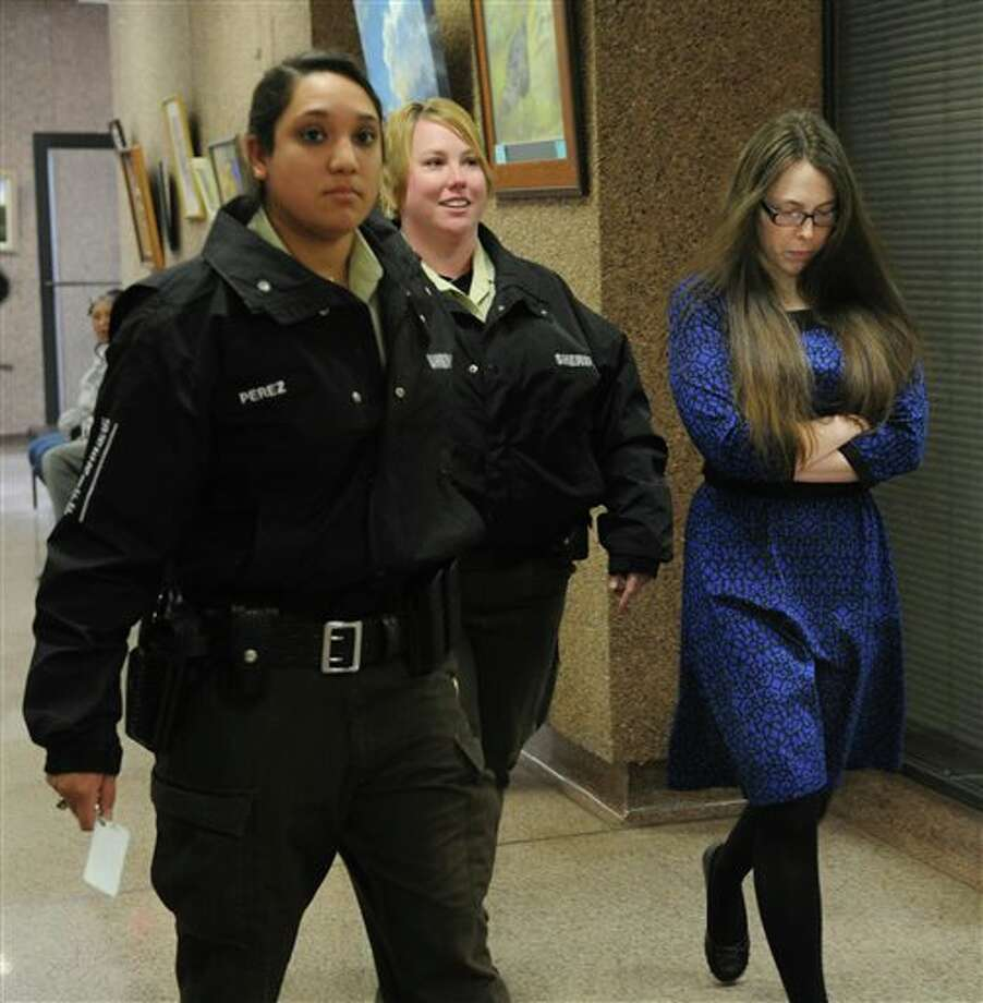 In this photo from Jan. 27, 2014, escorted by sheriff's deputies, Tiffany Klapheke, right, leaves the jury selection room at the Taylor County Courthouse in Abilene, Texas. Klapheke is with injury to a child in the August 2012 death of her 22-month-old daughter, Tamryn Klapheke, who died of malnutrition and dehydration. (AP Photo/Abilene Reporter-News, Nellie Doneva) Photo: Nellie Doneva / Abilene Reporter-News