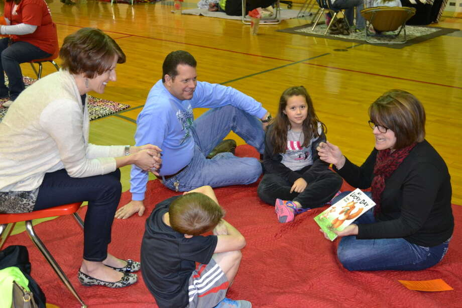 At Greenwood Elementary School's Fall in Love with Reading Café, teacher Kerri Latham reads to Trina Payton and her son Dylan and Jeff Wiginton and his daughter Katelyn. Photo: Photos Courtesy Of Heather Bennett