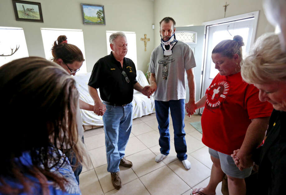 Hollas Hoffman, third from left, a chaplain, says a prayer with John Salmon, a truck driver with Wrangler Trucking, and his wife Rebecca Salmon, shown to Hoffman's right, and other family members Wednesday, Feb. 4, 2015, in Gonzales, Texas. Hollas and his wife Nelda Hoffman, are the founders of Oil Patch Chaplains, who provide a support system to meet the spiritual and physical needs of the oil industry. Their ministry has twenty certified chaplains and over 40 volunteers. Salmon broke his neck Dec. 26, 2014 when the 18-wheeler he was driving flipped. ( Gary Coronado / Houston Chronicle ) Photo: Gary Coronado