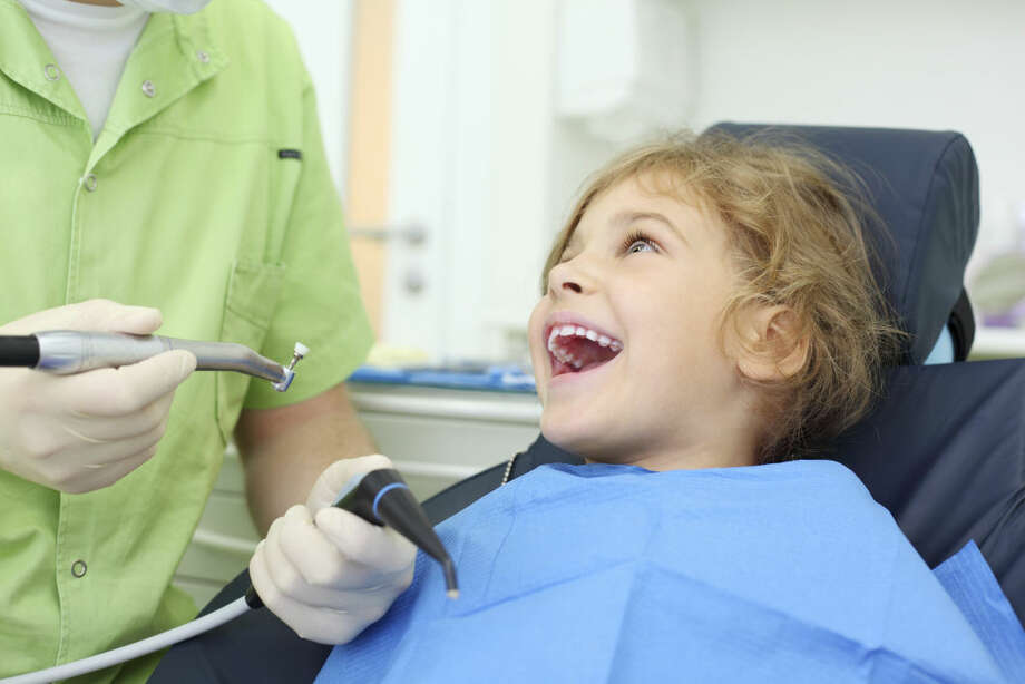 Dentist hands hold grinding drill, girl opens her mouth. Photo: Pavel Losevsky