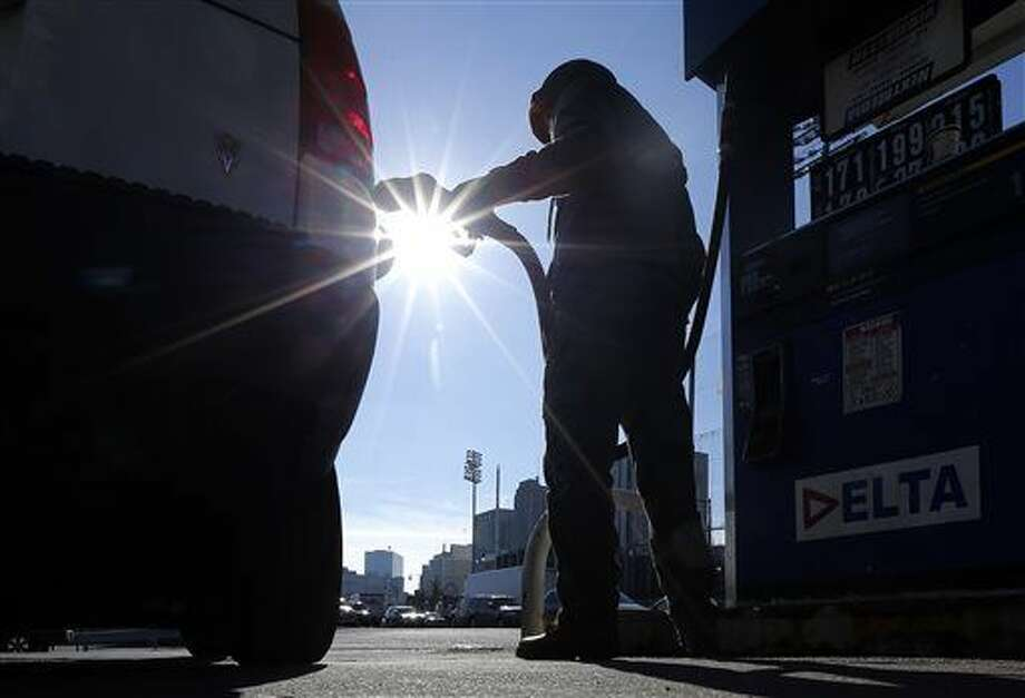 FILE - In this Jan. 23, 2015 file photo, Sonu Singh pumps gas for a motorist at a Delta gas station in downtown Newark, N.J.(AP Photo/Julio Cortez, File)