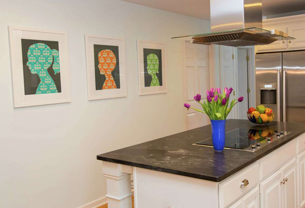 A sleek contemporary kitchen gets a pop of color from a trio of modern silhouettes by Ridgefield artist Antonio Munoz.