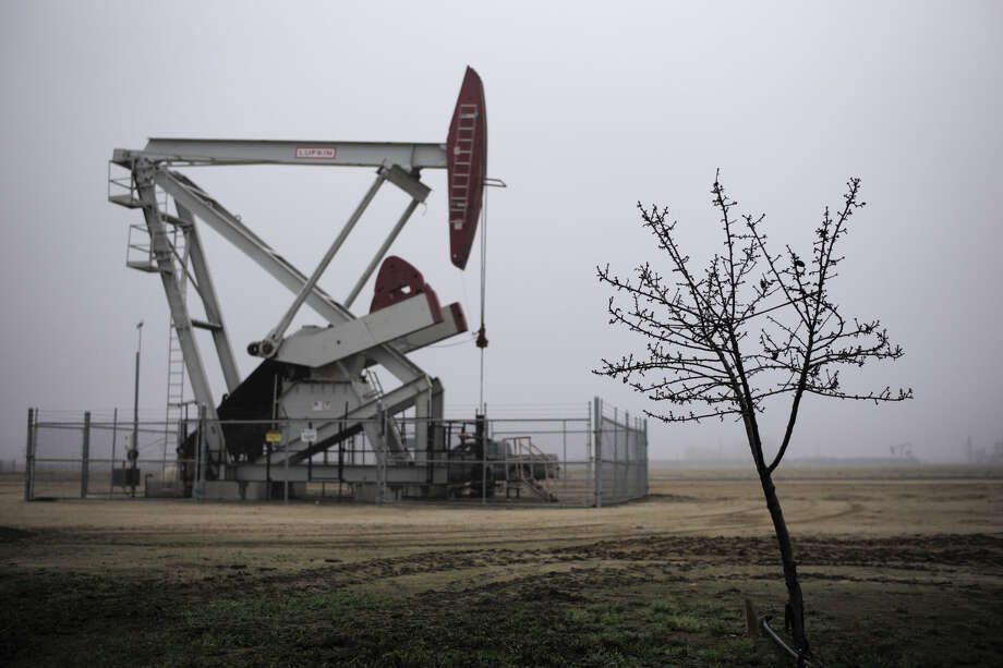 An almond tree stands in front of a pumpjack, Thursday, Jan. 15, 2015. Photo: Jae C. Hong