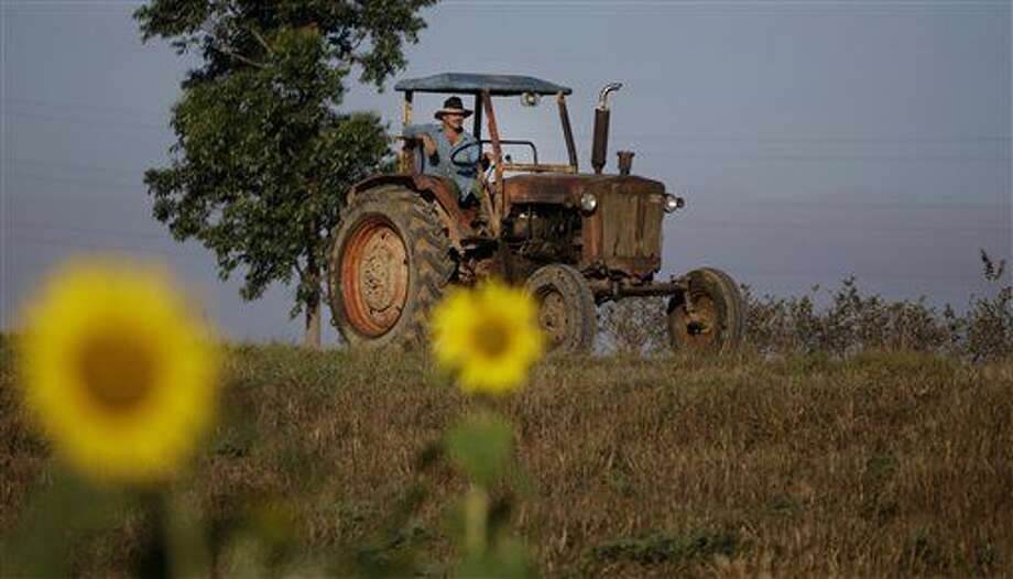 FILE - In this Feb. 22, 2011 file photo, a farmer drives his tractor in Pinar del Rio, Cuba. The Obama administration has approved the first U.S. factory in Cuba in more than half a century, allowing a pair of former software engineers to build a plant assembling as many as 1,000 small tractors a year. The partners were notified by Treasury Department officials in February 2016. (AP Photo/Javier Galeano, File) Photo: Javier Galeano