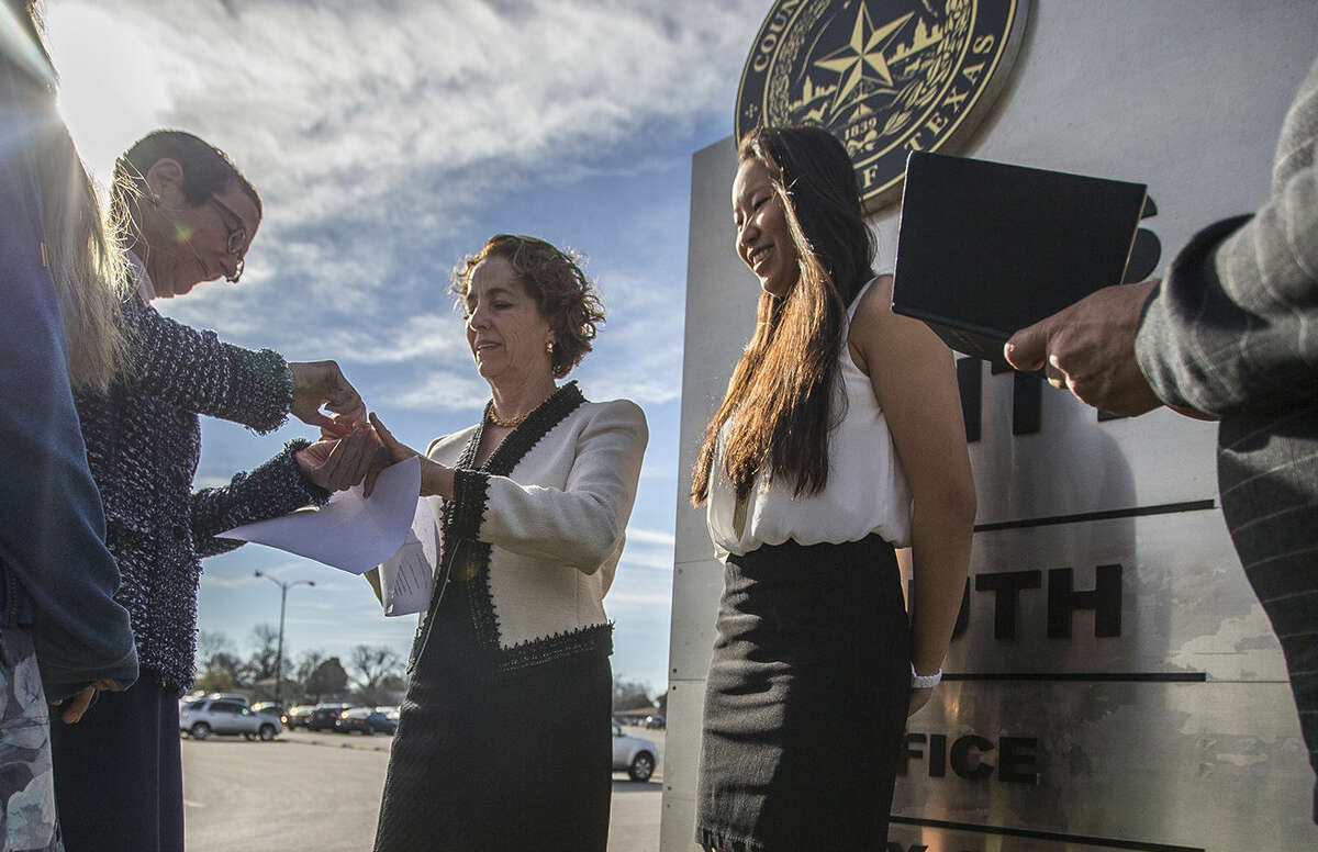 Sarah Goodfriend places the ring on Suzanne Bryant's ring finger as their daughters Ting , far left and Dawn look on, during the marriage ceremony with Rabbi Kerry Baker outside of the Travis County Clerk's office in Austin, Texas on Thursday, Feb. 19, 2015. The marriage followed a state District Court order instructing that officials not rely on Texas' unconstitutional prohibitions on same-sex marriage. Texas' decade-old, voter-approved ban on gay marriage was declared unconstitutional in federal court last year, but the judge stayed the ruling to allow the state to appeal. (AP Photo/Austin American-Statesman, Ricardo B. Brazziell) AUSTIN CHRONICLE OUT, COMMUNITY IMPACT OUT, INTERNET AND TV MUST CREDIT PHOTOGRAPHER AND STATESMAN.COM, MAGS OUT