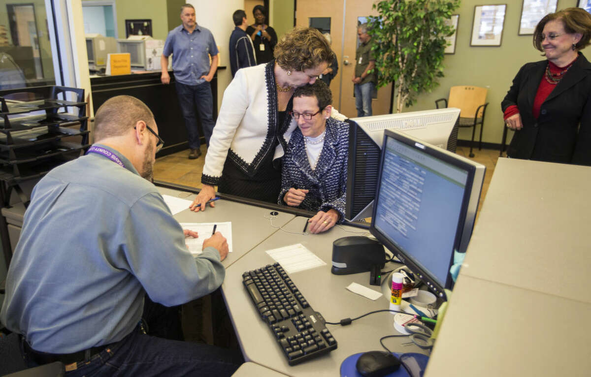Suzanne Bryant, left, and Sarah Goodfreind hug as recording specialist Michael Mitchell for the Travis county clerk's office records the final paper work of their marriage certificate on Thursday, Feb. 19, 2015 in Austin, Texas. Travis County spokeswoman Ginny Ballard said the marriage occurred Thursday, though it wasn't immediately clear if the license has legal standing. The marriage followed a state District Court order instructing that officials not rely on Texas' unconstitutional prohibitions on same-sex marriage. (AP Photo/Austin American-Statesman, Ricardo B. Brazziell) AUSTIN CHRONICLE OUT, COMMUNITY IMPACT OUT; INTERNET AND TV MUST CREDIT PHOTOGRAPHER AND STATESMAN.COM; MAGS OUT
