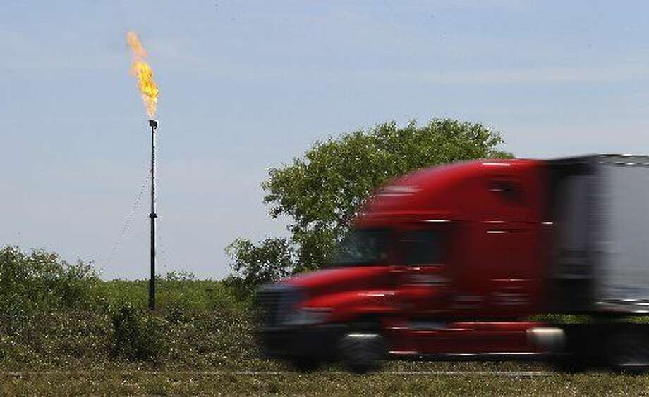 A commercial truck rolls past a flaring stack burning off excess gas in La Salle County near Cotulla, Texas. (Kin Man Hui/San Antonio Express-News) Photo: San Antonio Express-News