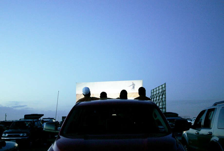 A group of patrons prepares to watch a movie on one of three large screens at the Big Sky Drive-In theater Friday. photo by Gary Rhodes 07/19/08 Photo: Midland