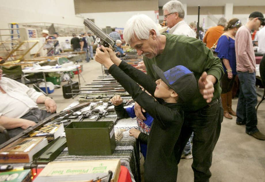 Ruben Prieto, age 8, checks out a .45 cal AMT 1911 pistol at the Silver Spur Gun & Blade Show on Saturday at Horseshoe Arena. James Durbin/Reporter-Telegram Photo: JAMES DURBIN