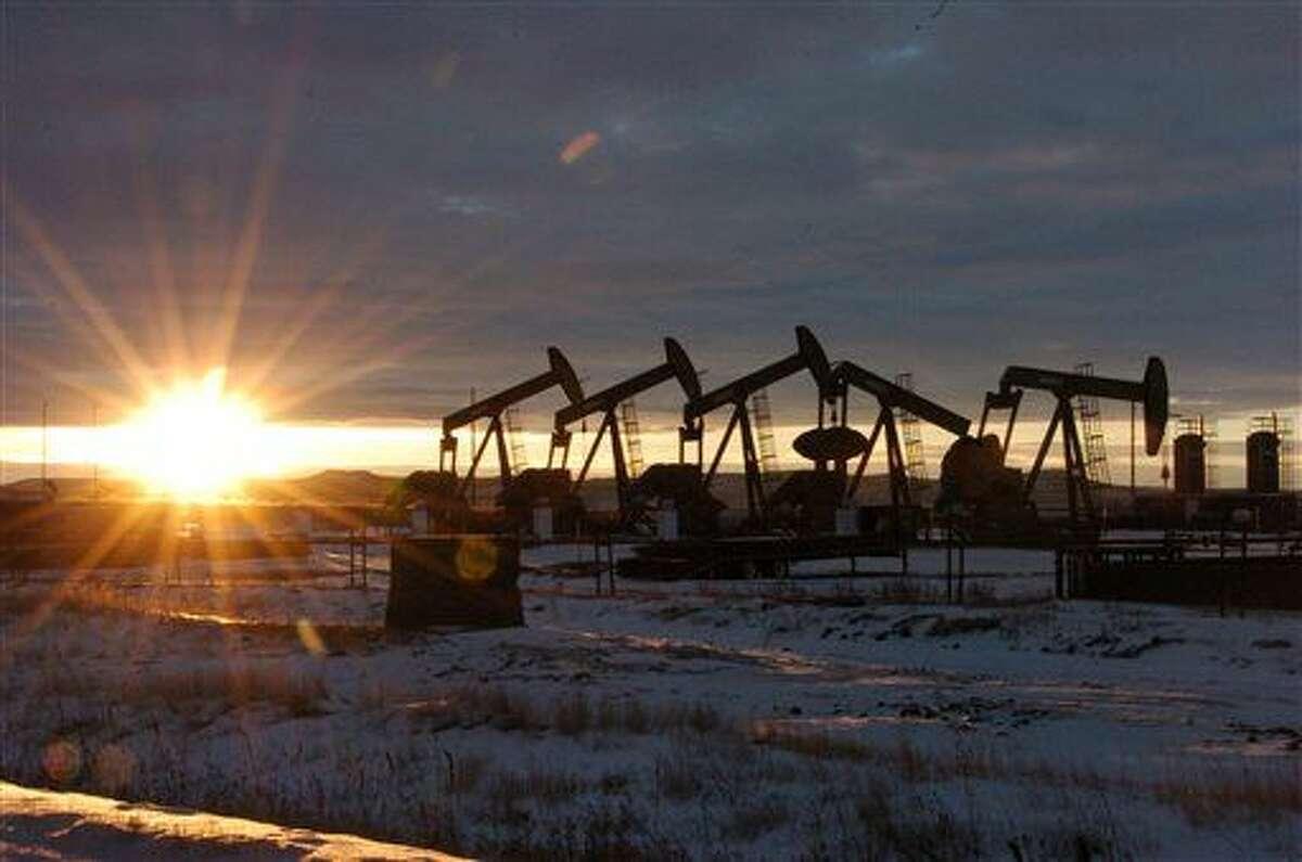 In this Wednesday, Jan. 14, 2015, photo, oil pump jacks are seen McKenzie County, in western North Dakota.