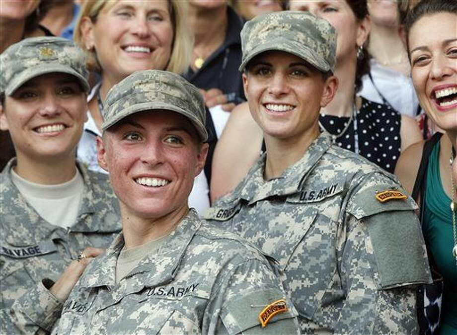FILE - In this Aug. 21, 2015, file photo, Army 1st Lt. Shaye Haver, center, and Capt. Kristen Griest, right, pose for photos with other female West Point alumni after an Army Ranger school graduation ceremony at Fort Benning, Ga. Haver and Griest became the first female graduates of the Army's rigorous Ranger School. The decision by the Pentagon to allow women to serve in all combat jobs has put new focus on an often-forgotten U.S. institution: the Selective Service. While America has not had a military draft since 1973, all men must register with the Selective Service within 30 days of turning 18. U.S. leaders repeatedly insist that the all-volunteer force is working and the nation is not returning to the draft. But there are increasing rumblings about whether women should now be required to register if they can indeed serve in all areas of the military. (AP Photo/John Bazemore, File) Photo: John Bazemore