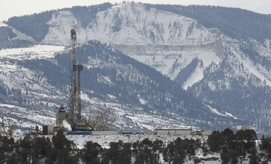 In this photograph taken Thursday, Feb. 28, 2013, near Parachute, Colo., the drill rig at a natural gas site stands with mountains in the background on Colorado's Western Slope. A campaign to get universities to stop investing in greenhouse gas-producing fuels has come deep into energy country as activists will ask the University of Colorado to divest from coal and peteroleum companies. (AP Photo/David Zalubowski) Photo: David Zalubowski