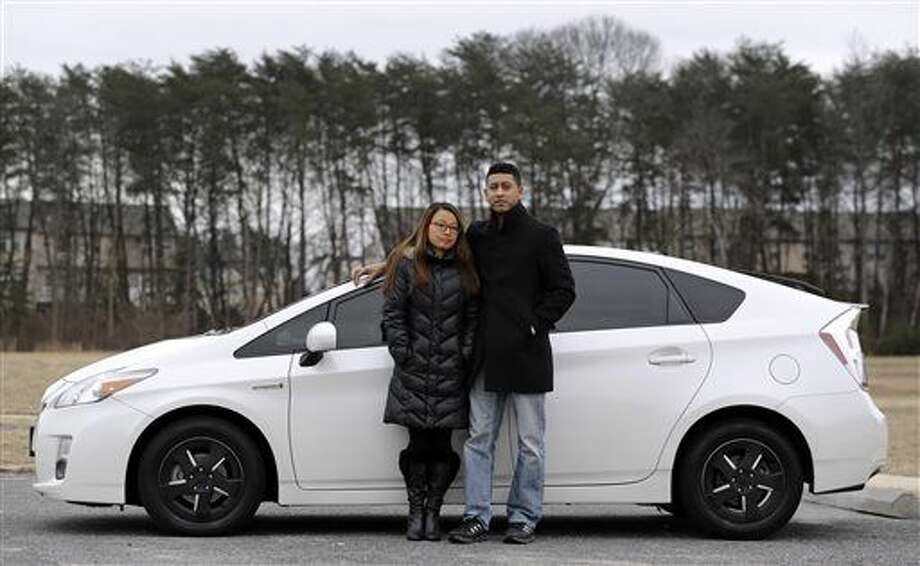In this Feb. 14, 2015 picture, Eri and John Castro pose in front of their 2011 Toyota Prius in Glen Burnie, Md. The Castros bought the pre-owned car last year, only to find out after they got it home that it was under recall because it could stall without warning. (AP Photo/Patrick Semansky) Photo: Patrick Semansky